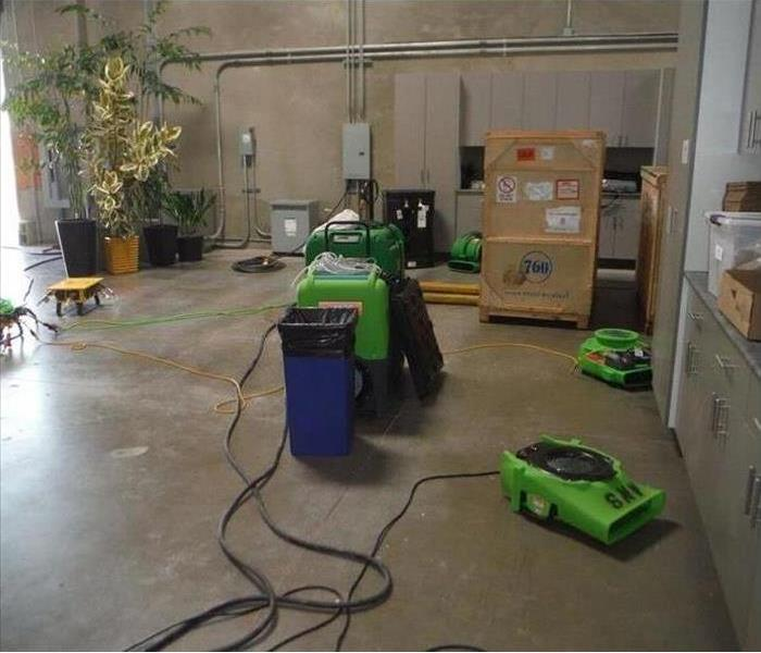 Green dehus and air movers set up to dry out warehouse