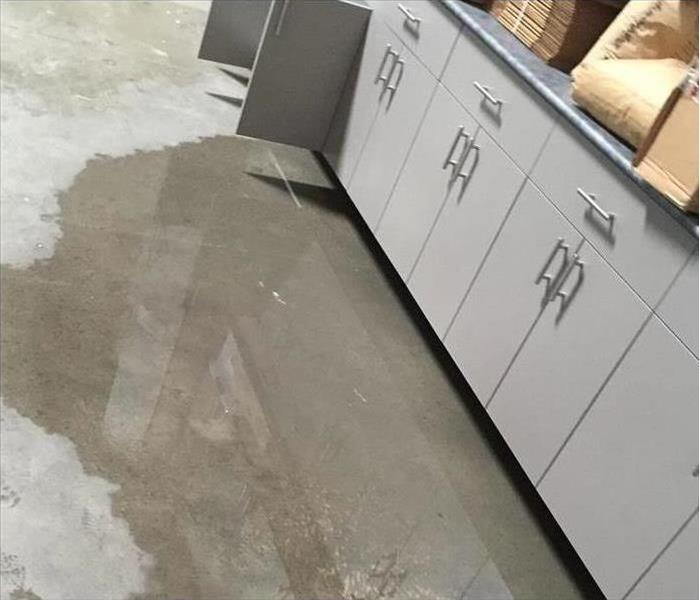 Water flooded on the grey flooring of a warehouse of a business