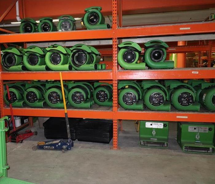 Green equipment stacked in a warehouse.