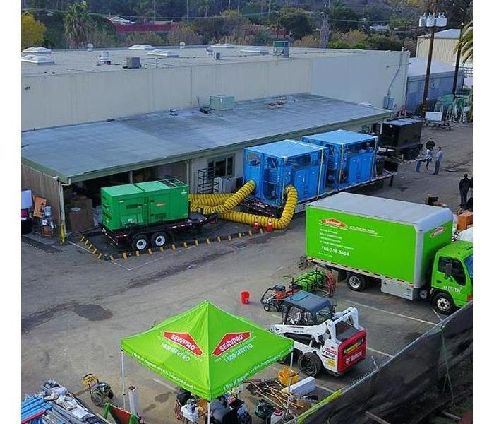 Green trucks and contents set up at a school parking lot.