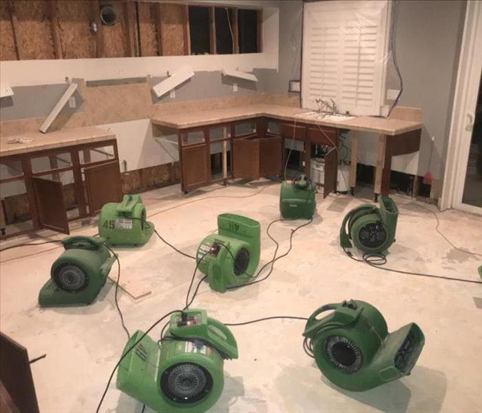 Green air movers and dehumidifiers in large room.
