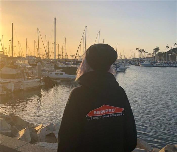 Girl standing looking at the sunset over the bay wearing black SERVPRO hoodie.
